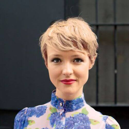 blonde Frau blaues Hemd Pixie cut